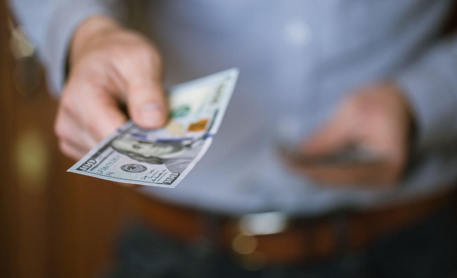 man handing over a one hundred dollar bill