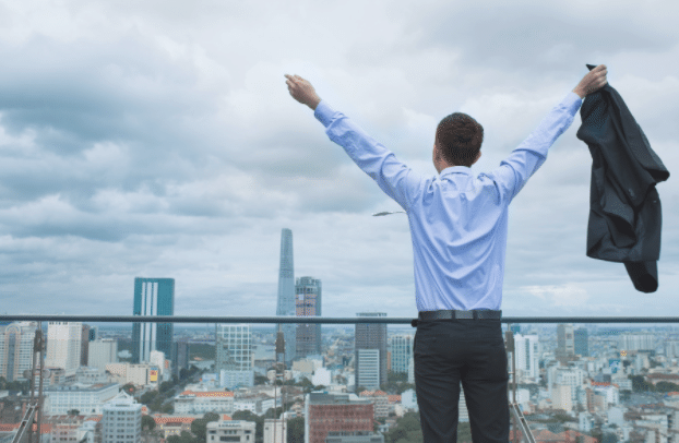man overlooking large city while raising his hands in joy